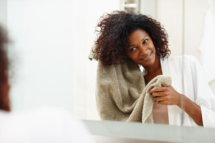 Woman drying her natural hair with a towel.