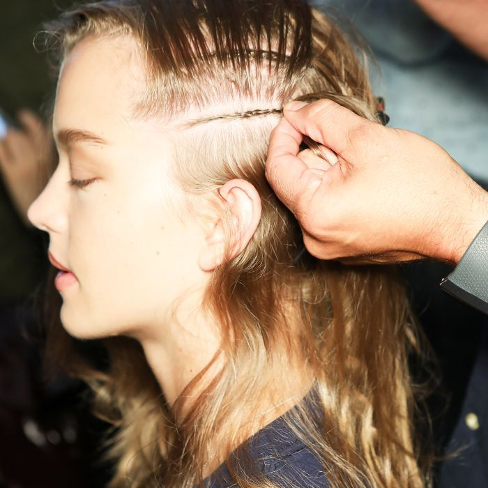 Model having her hair braided backstage