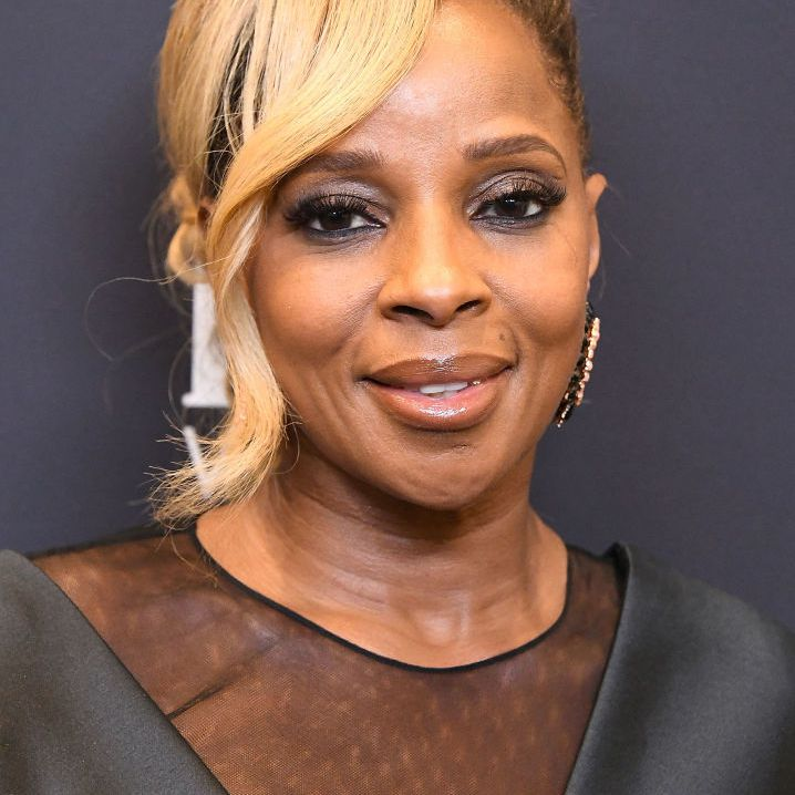 Mary J. Blige blonde updo with side-swept tendril bang