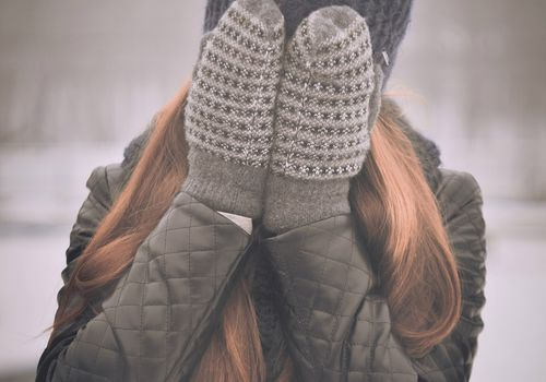 woman covering face with gloved hands