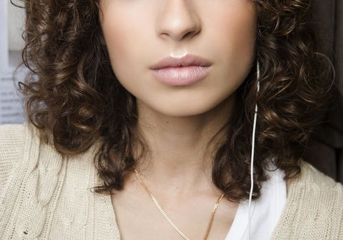 woman with short curly hair and clear skin