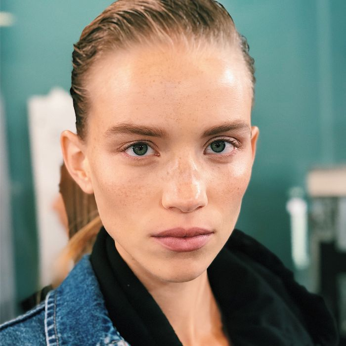 Model with blonde hair slicked back and freckles
