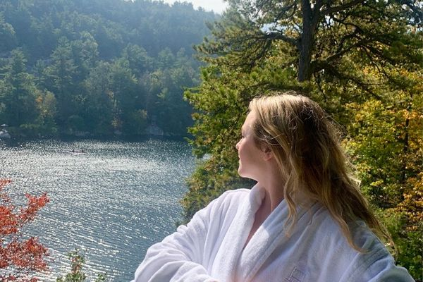 woman in robe looking out at water