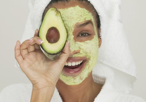 Portrait of a young woman wearing a facial mask holding a slice of avocado