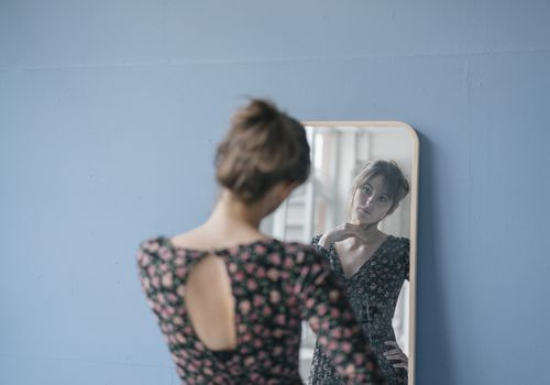 Young woman wearing a floral dress, looking in a mirror