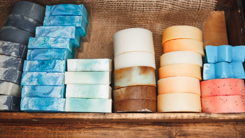 Castile and natural bar soap against burlap on a wood shelf.