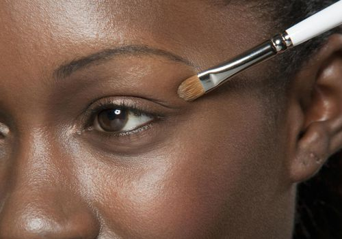 Woman applying eye shadow to her eyelids