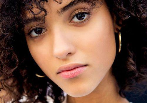 girl with brown curly hair and hoop earrings