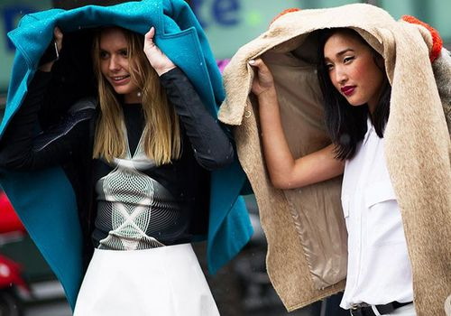 Two women holding their coats above their heads to shield themselves from the rain.