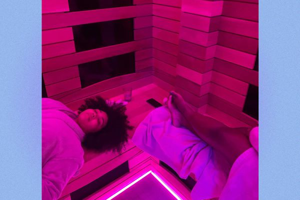 Women lounge in a sauna, with purple infrared lighting