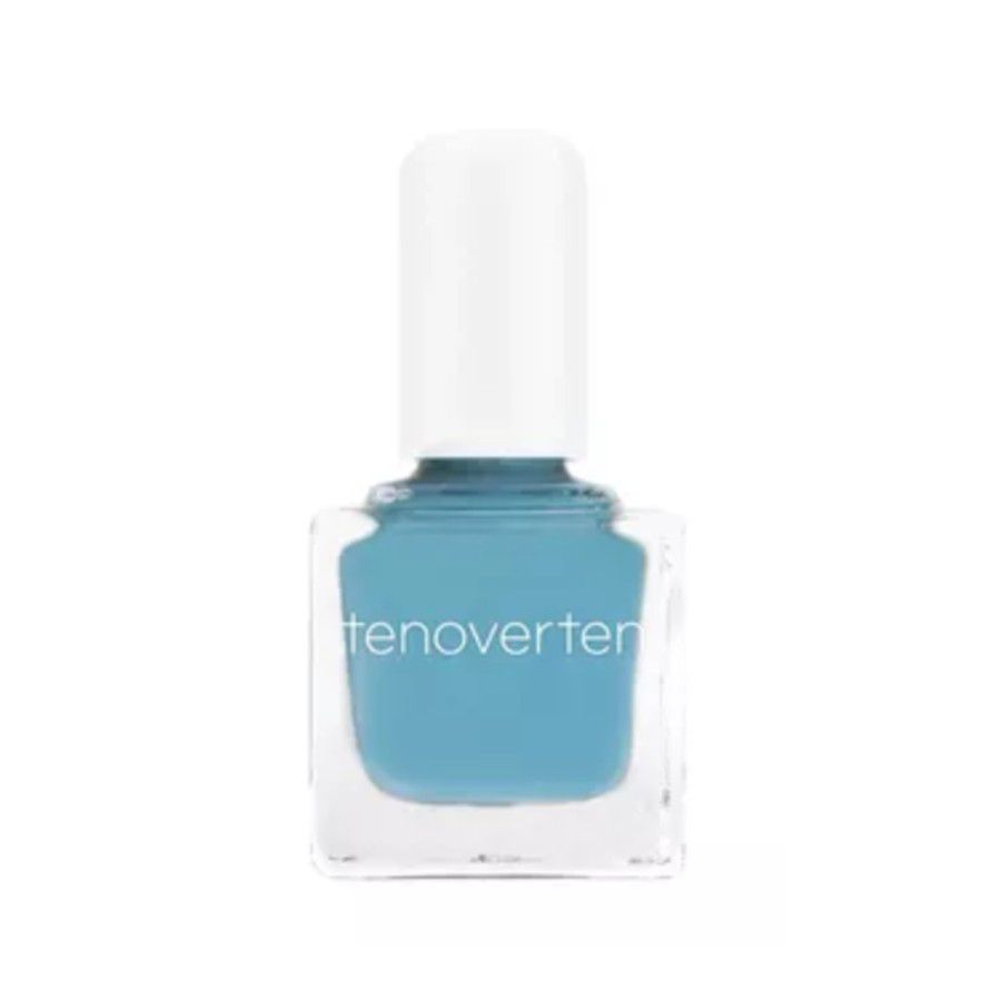 Bottle of dusty blue nail polish on a white background.
