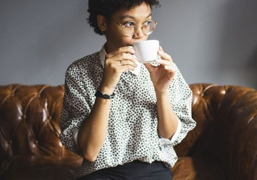 woman drinking from coffee cup sitting on couch