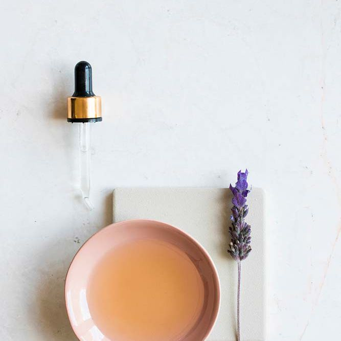 dish with tea tree oil and sprig of lavender