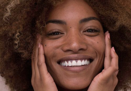 woman touching her face smiling