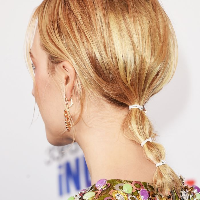 Saoirse Ronan wearing a short, messy ponytail with multiple hair ties