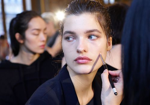 Model getting her makeup applied backstage at a fashion show