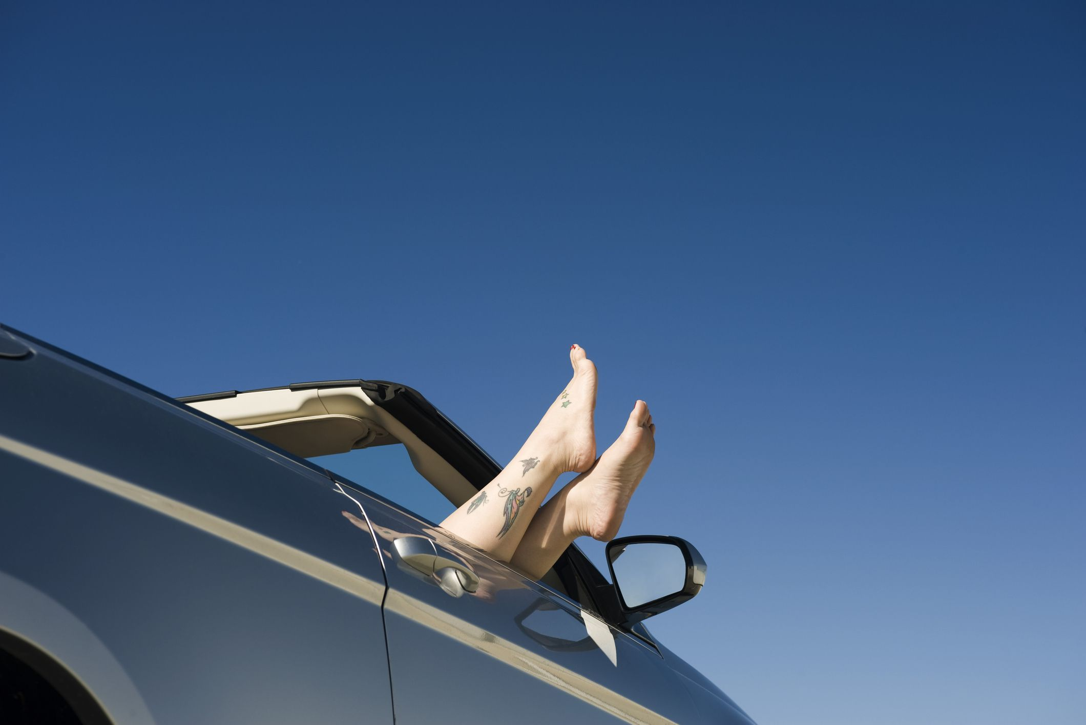 convertible with person feet hanging out window