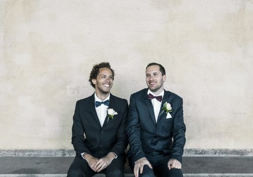 Grooms sitting side by side