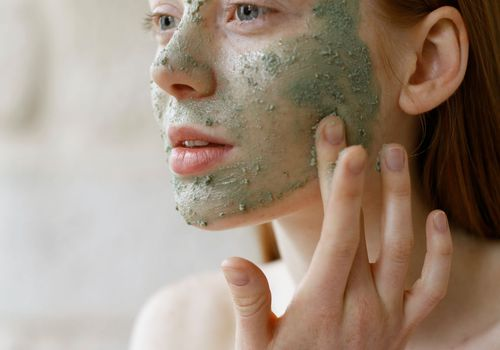 woman applying face mask to her face