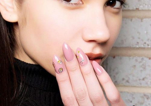 woman with nail design touching face