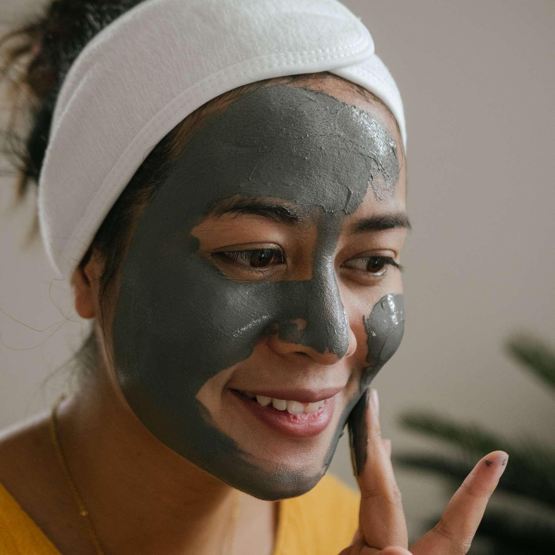 woman applying charcoal mask