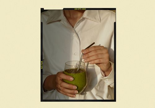 person holding green smoothie