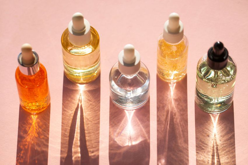From above bottles with various moisturizing products arranged in line on pink background