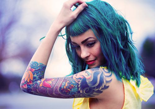 Woman with a sleeve tattoo, blue hair, and bangs