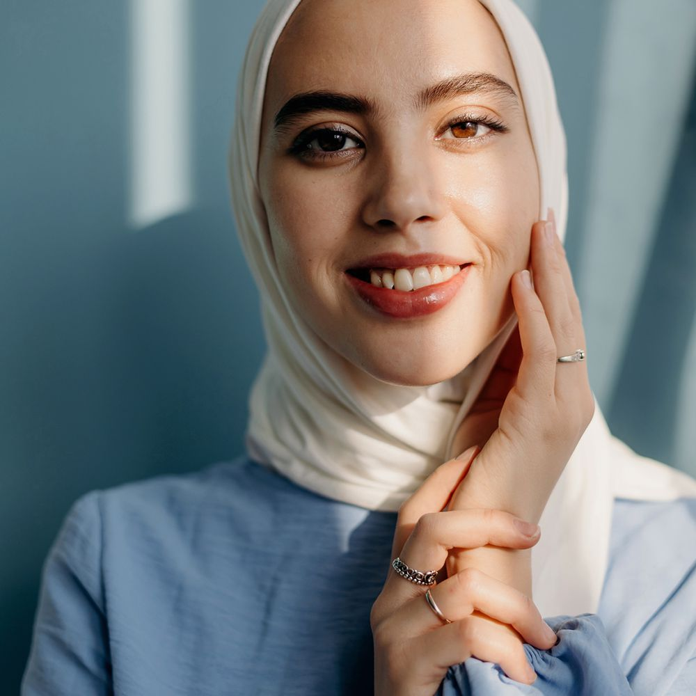 person in hijab smiling in sunlight