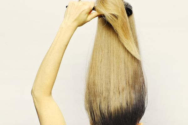 Woman with root growth brushing her hair up