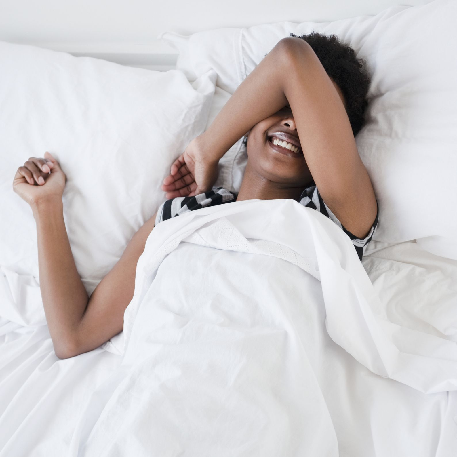 Woman laying in bed with arm over face