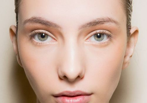 model with dark blonde hair and pale skin wearing a small amount of orange eyeshadow