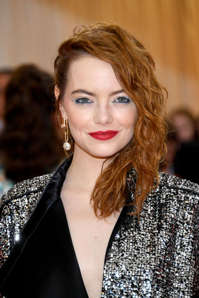 Emma Stone deep side-parted wavy, wet mid-length hair