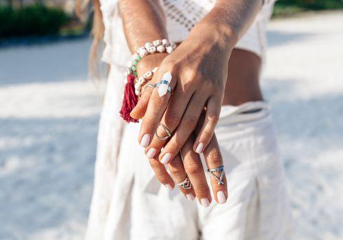 Crossed hands wearing multiple rings