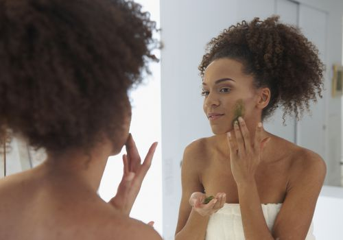 Woman rubbing exfoliant on face at mirror