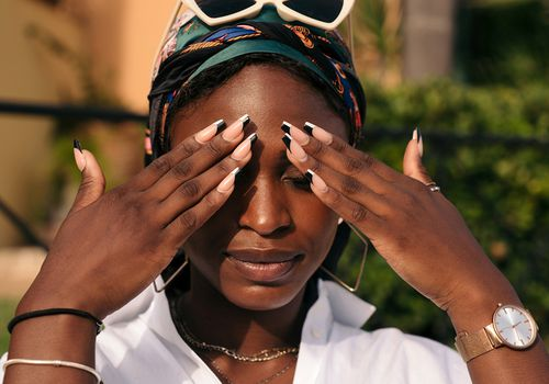 black woman in sun light with acrylic nails