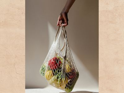 Woman holding shopping bag of fruits and veggies