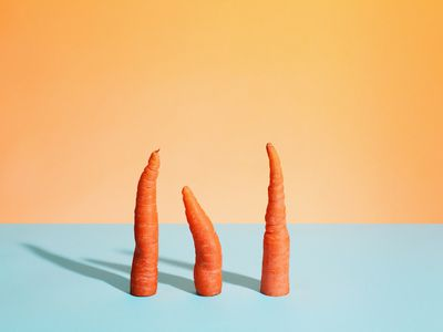 Three cut carrots standing on a flat surface