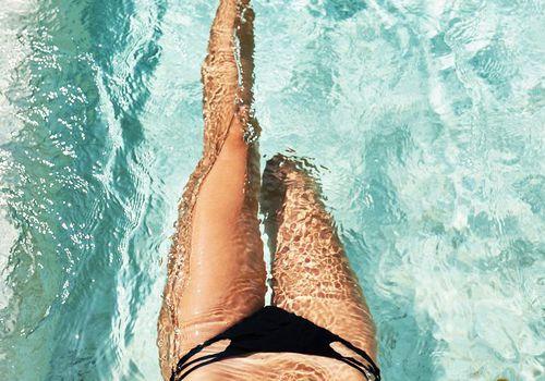 womans legs in bikini in pool