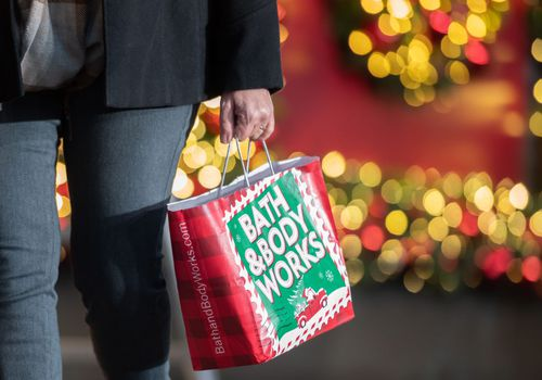 hand holdintg a Bath and Body Works holiday shopping bag