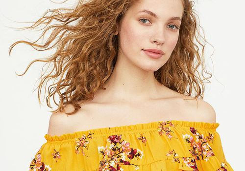 woman with red hair wearing yellow floral peasant top