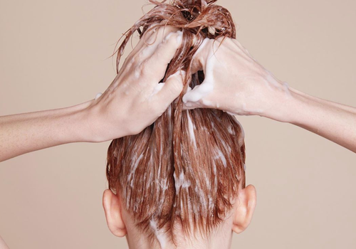 woman applying hair mask to red hair