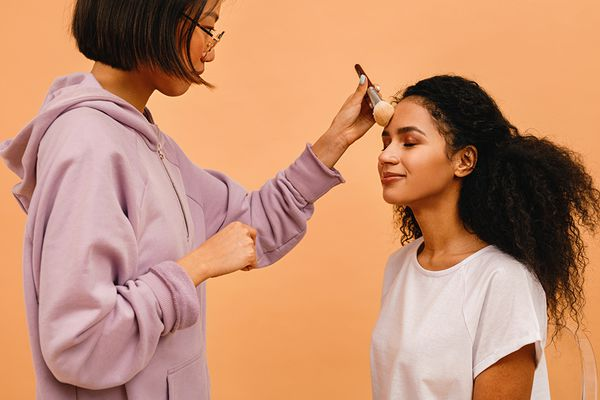 young woman getting makeup done in studio
