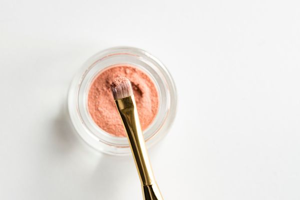 Makeup brush with dipped in pigment from paint pot