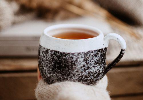 hand holding a mug of herbal tea