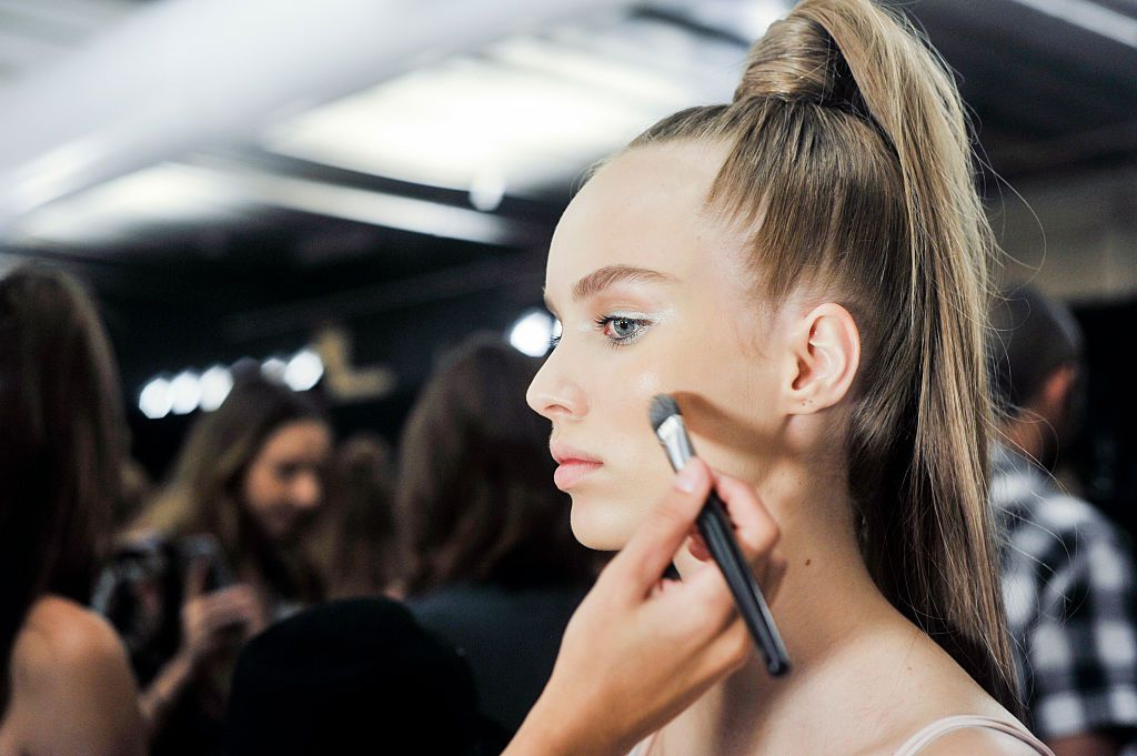 Girl getting makeup done before runway show
