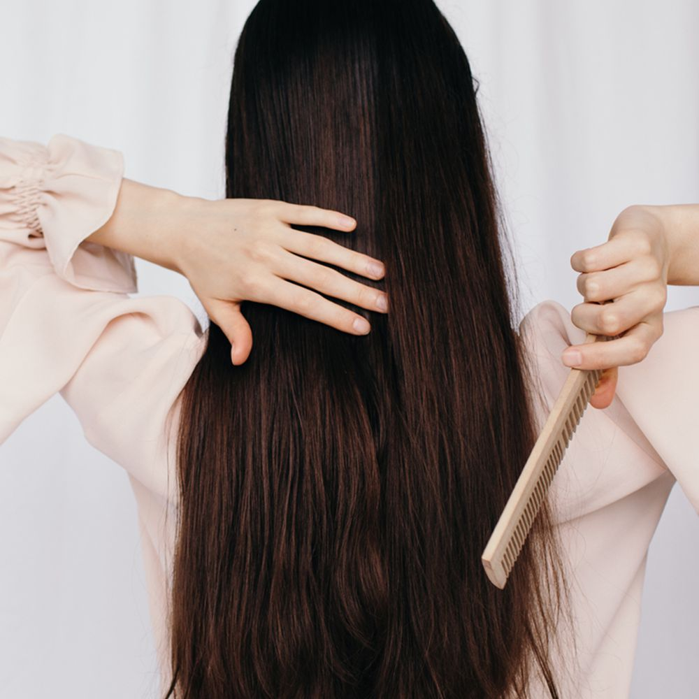 person combs long thick healthy hair