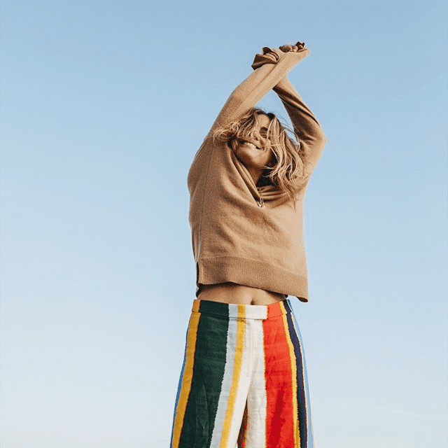 Smiling woman with brown sweater and striped pants raising her arms in the air.