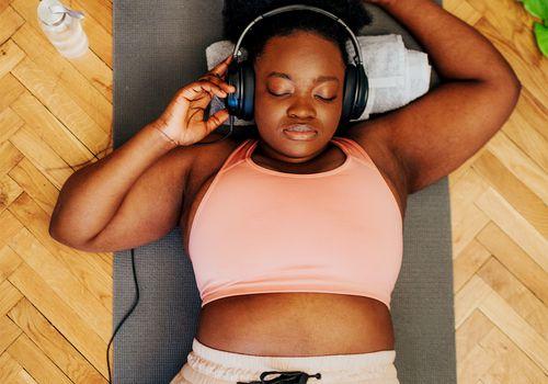 black femme lying on mat after workout