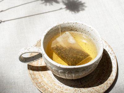 warm mug with tea and teabag in sunglight